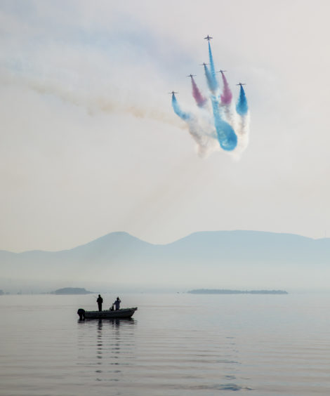 The Royal Air Force aerobatic team, the Red Arrows, performing the 'Goose' manoeuvre on a very still morning whilst fisherman watch on in Chalkoutsi, Greece.
