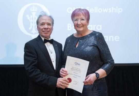 Barbara MacFarlane receiving her award from Professor Sir Lewis Ritchie.