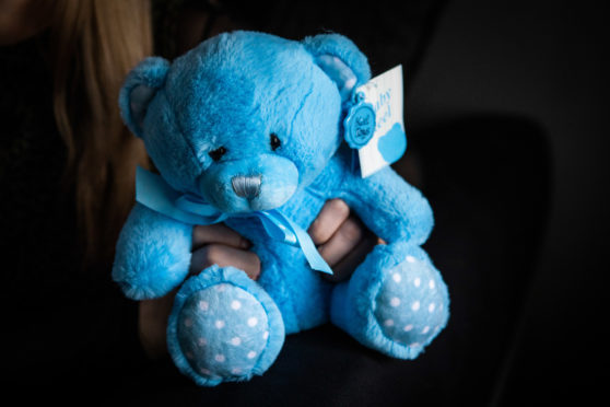 Ashley Stevens holding a teddy bear that was for her baby, Noah.