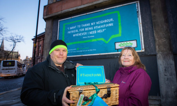 Mick Vine and Patricia Phinn with their billboard in the background.