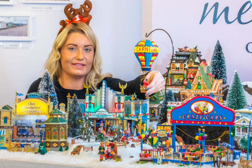 Staff member Abbie Durham with the model Christmas village.
