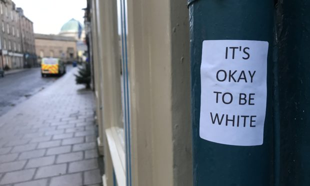 """Stickers reading """"Its okay to be white"""" have appeared around Perth."""