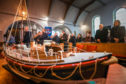 Members of the RNLI squad in the front rows of the church with a model of the Mona Lifeboat