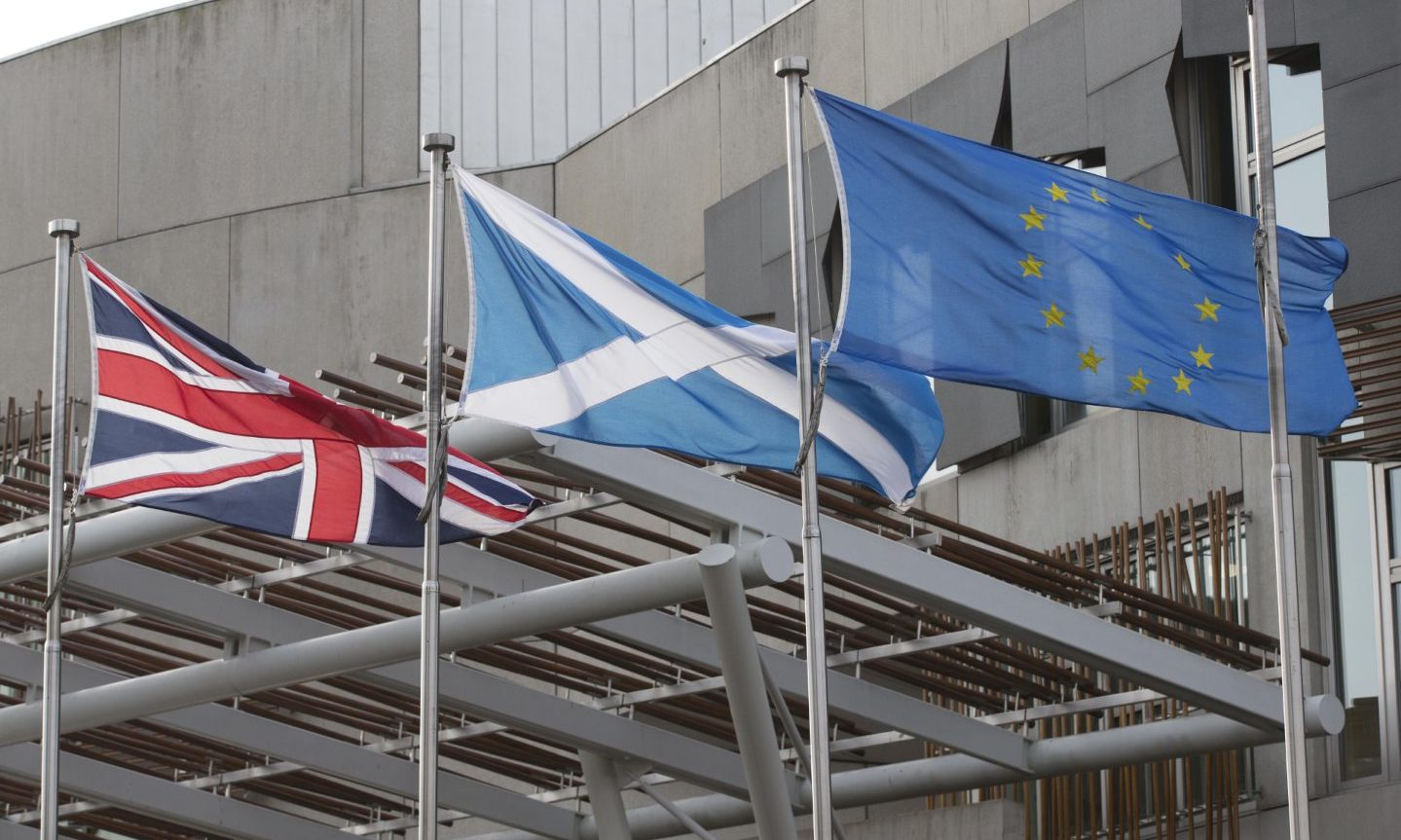 The flags of the United Kingdom, Scotland and the European Union outside The Scottish Parliament building.
