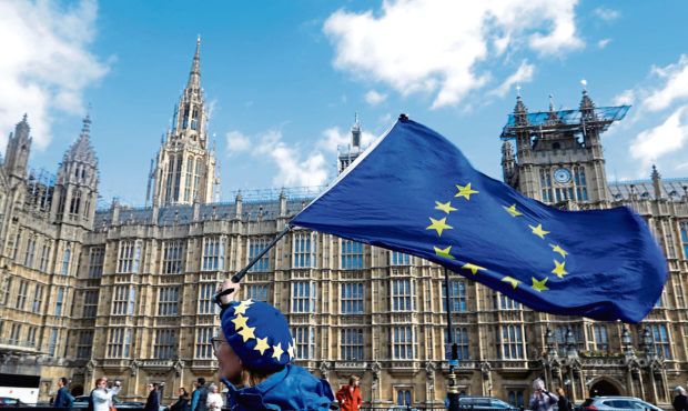 An anti Brexit campaigner shows her support for Europe waving a European Union flag outside Parliament in London