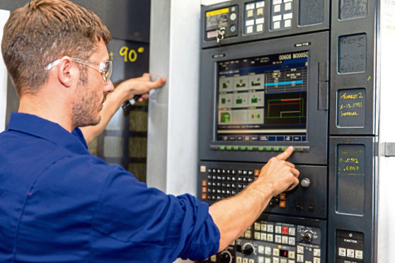 A GA Engineering worker operates a drilling lathe.