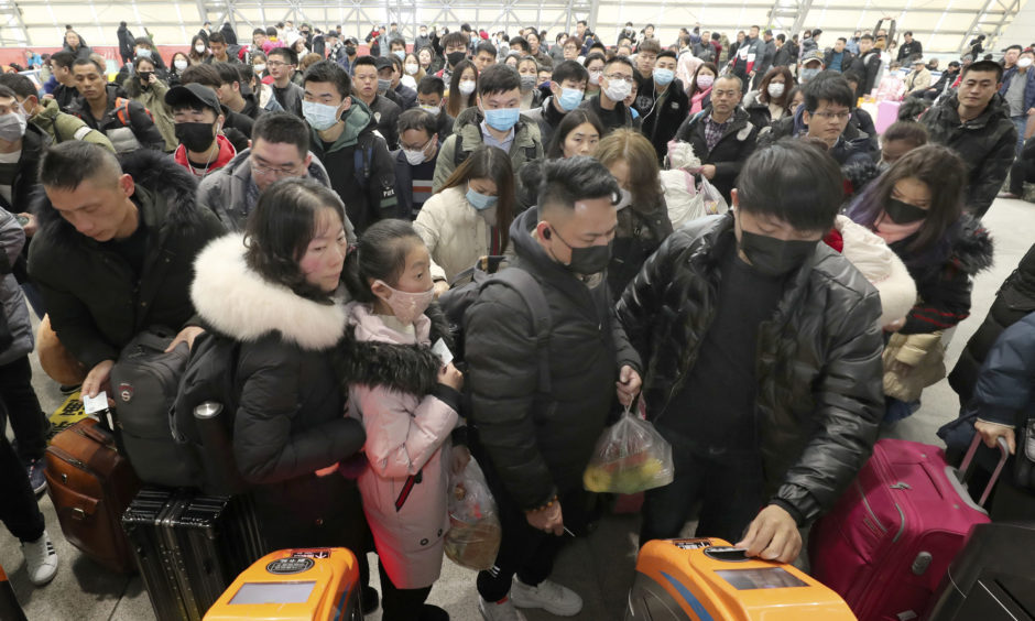 Travellers wear face masks as they line up at turnstiles at a train station in Nantong, eastern China, at the start of the coronavirus outbreak in January 2020.