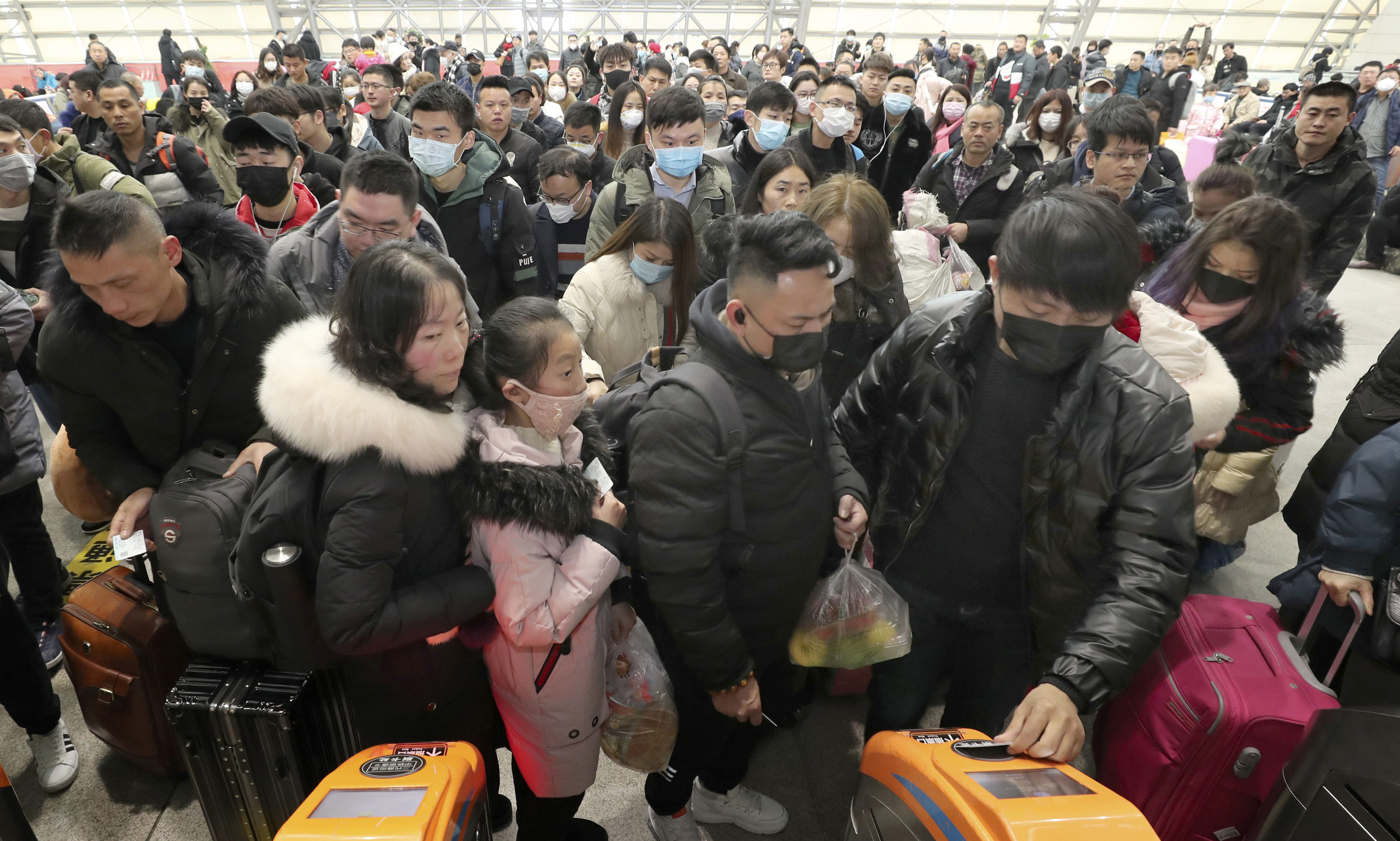 Travellers wear face masks as they line up at turnstiles at a train station in Nantong, eastern China