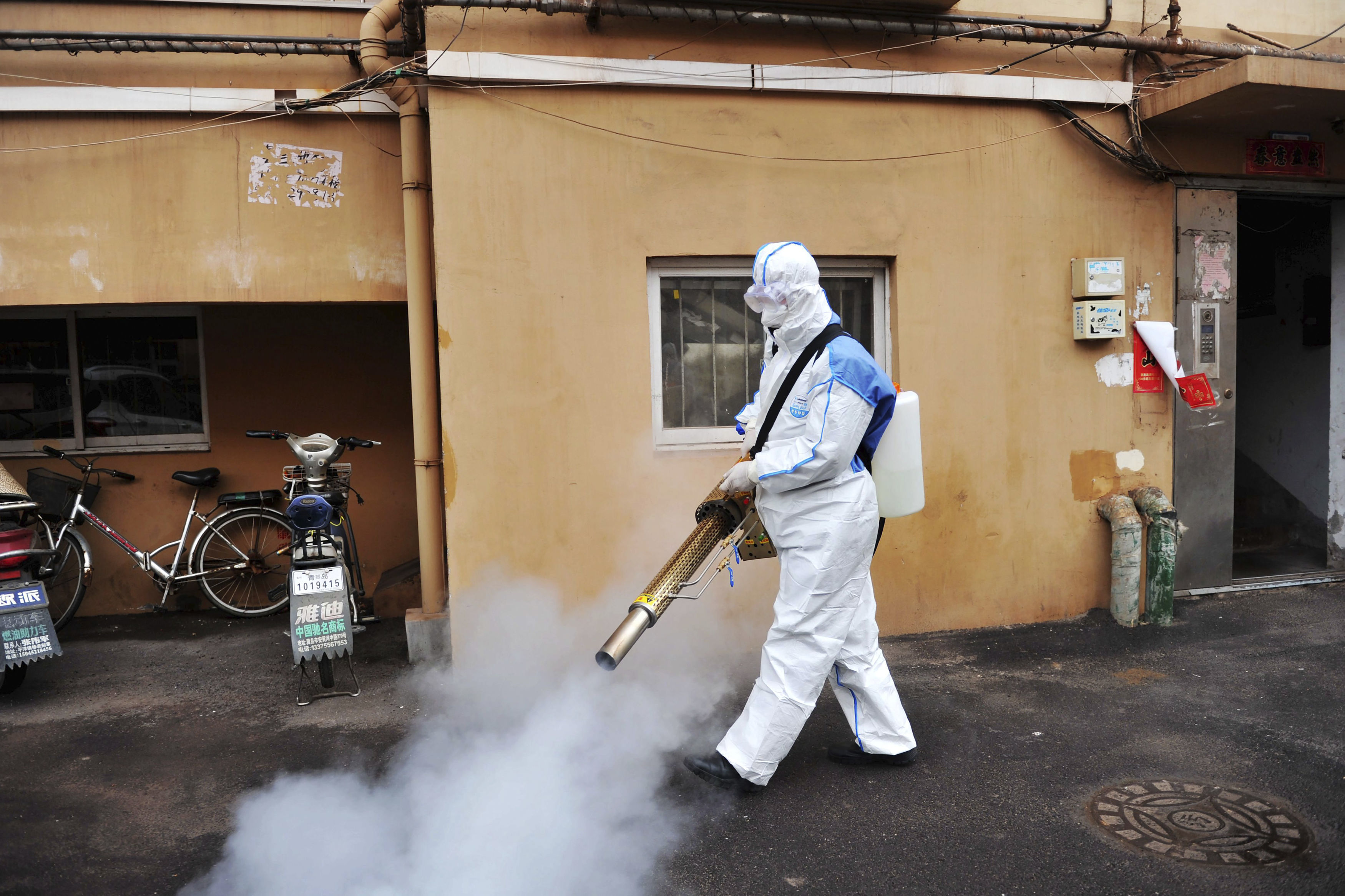 A worker wearing a protective suit sprays disinfectant in Qingdao in eastern China's Shandong Province.