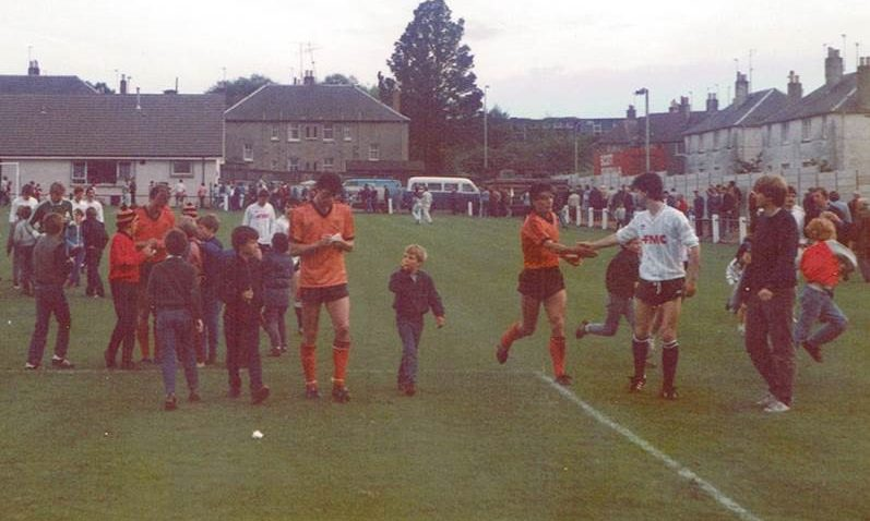 David Narey (centre) and Eamonn Bannon sign autographs for young fans following a match between St Andrews United and Dundee United at Recreation Park while Stuart Beedie shakes hands with an opponent. 30 July 1985. The game finished 5-1 for the tangerines.