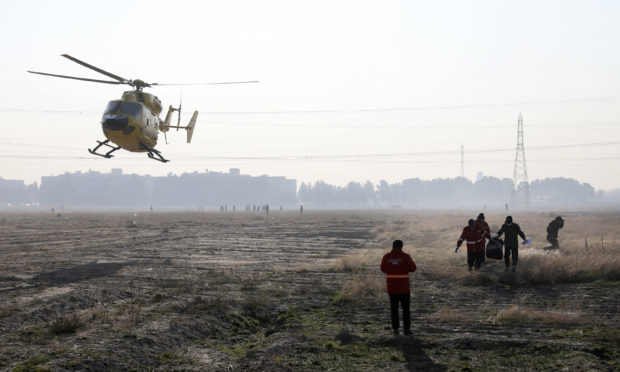 A rescue team work at the scene where an Ukrainian plane crashed in Shahedshahr, southwest of Tehran, Iran.