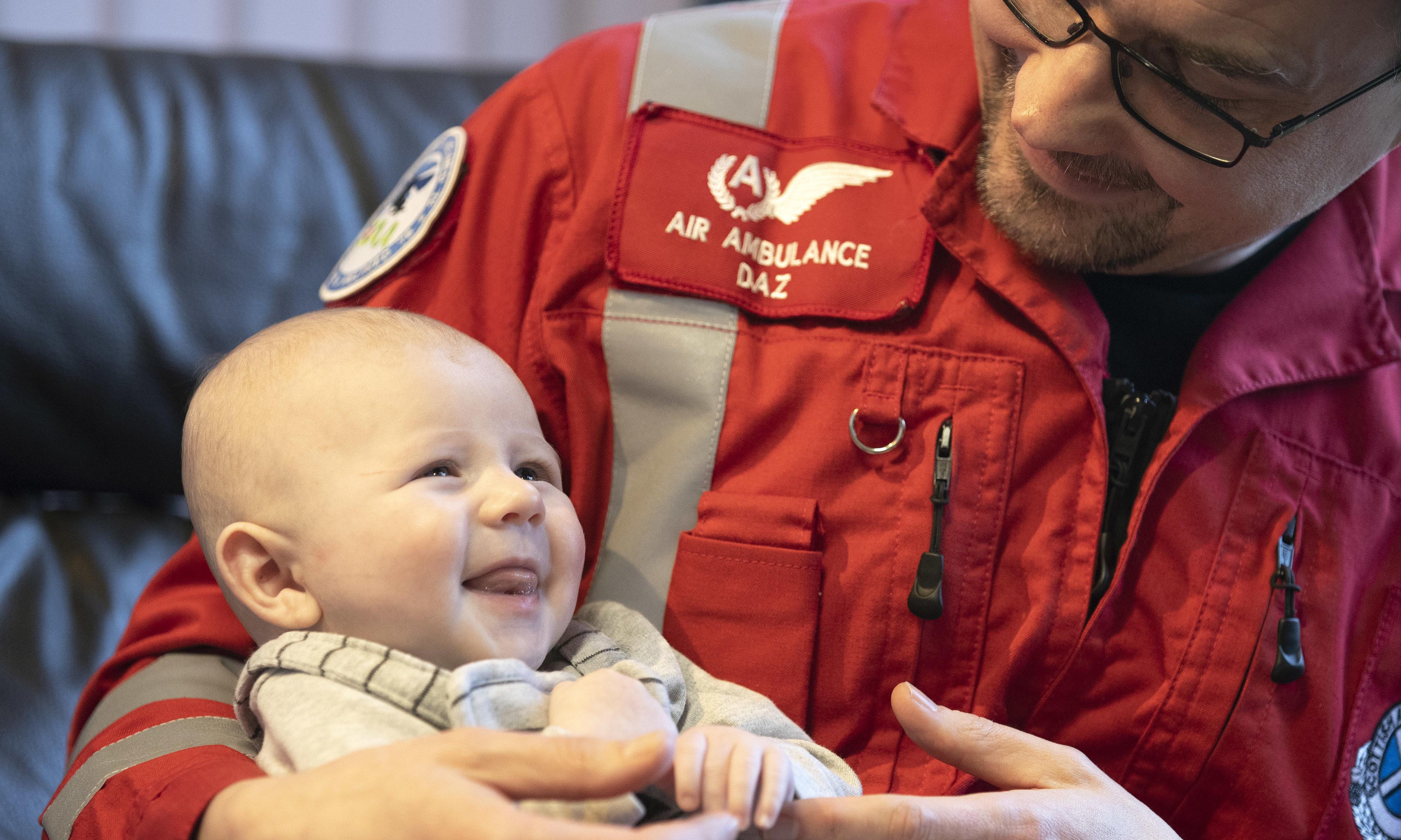 Paramedic Darren O'Brien holding baby James.