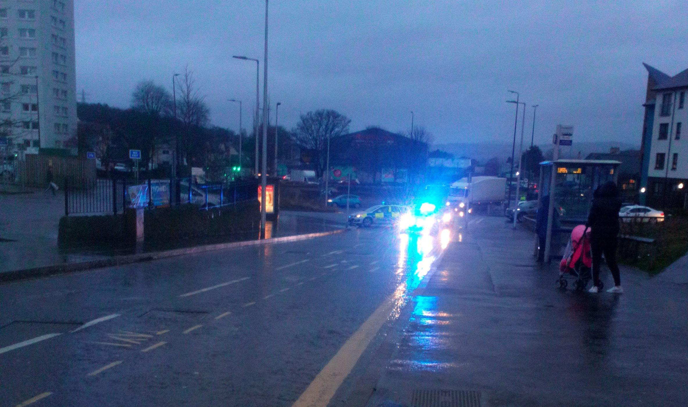 A police vehicle on Lochee High Street after a crash involving a bus and an elderly pedestrian.