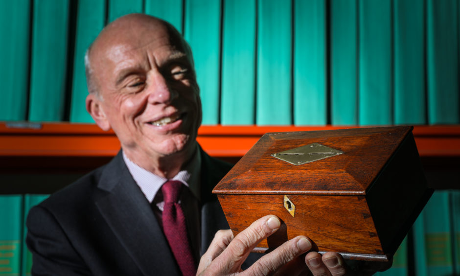 Journalist and Historian Norman Watson with a money box made from the wood of one of the Tay Bridge Disaster train carriages.