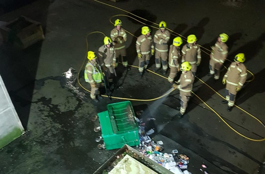 Firefighters tackle the bin fire at the foot of Pomarium Street flats, Perth.
