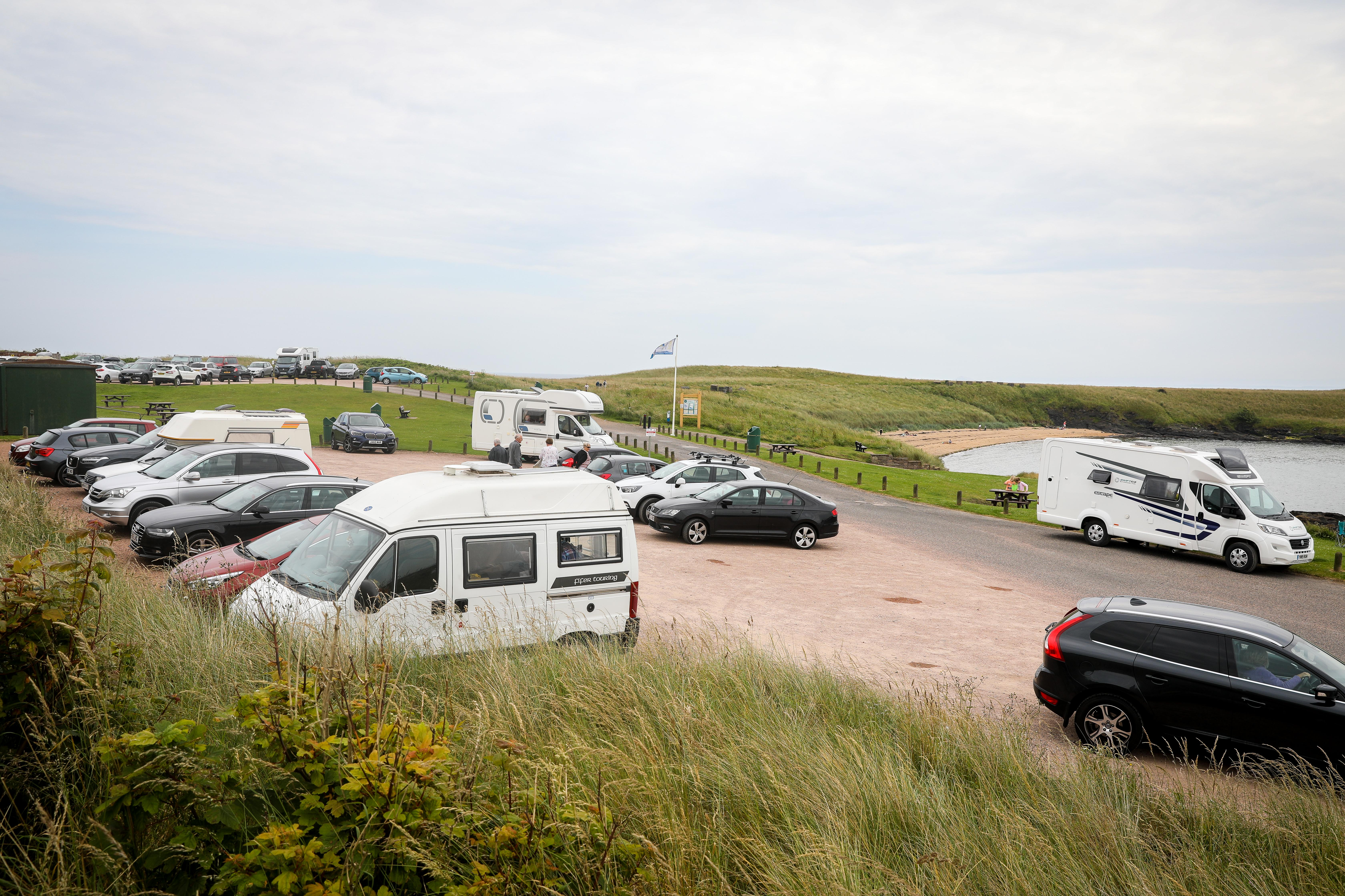 Campervans and cars filling up the car park and roadside as tourists arrive in campervans to enjoy Fife.