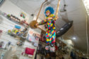 The clown back in place performing in the window of The Present Shop, Mercat Shopping Centre