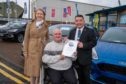 Social Security Secretary Shirley-Anne Somerville with Kenneth Harper and Alastair Aitken, Motability specialist at Macklin Motors in Dunfermline.