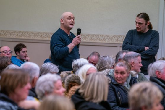 Members of the public address a packed public meeting.