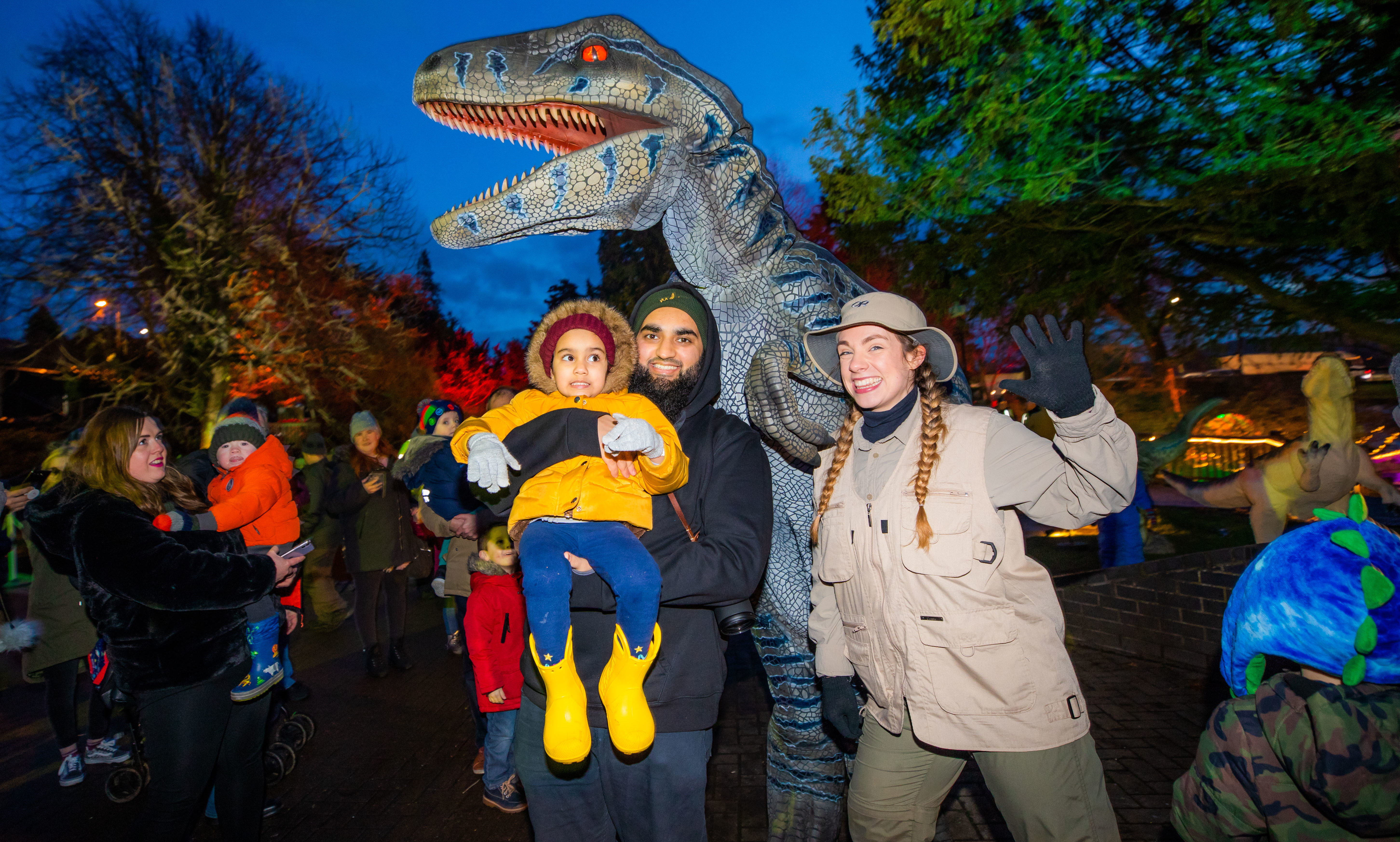 Ifran Ali and daughter Saarah Ali (aged 3, correct spelling) from Perth get up close to one of the dinosaurs Ritchie the Raptor alongside Ranger Georga.