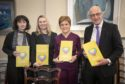 Chair Fiona Duncan, panel member Laura Beveridge, First Minister Nicola Sturgeon and Deputy First Minister John Swinney with copies of the Independent Care Review report at Bute House, Edinburgh.