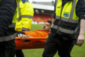 Osman Sow is carried off at Tannadice.