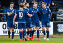 The Dundee players celebrate Kane Hemmings' second strike.