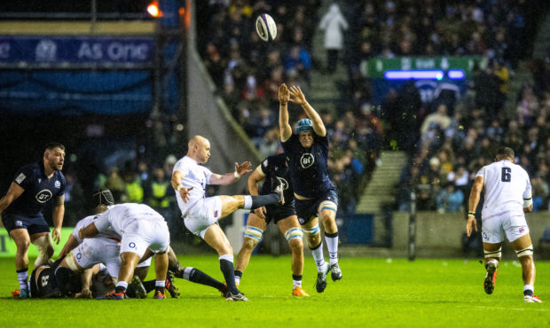 Scotland's Scott Cummings charges down Willie Heinz's attempted kick.