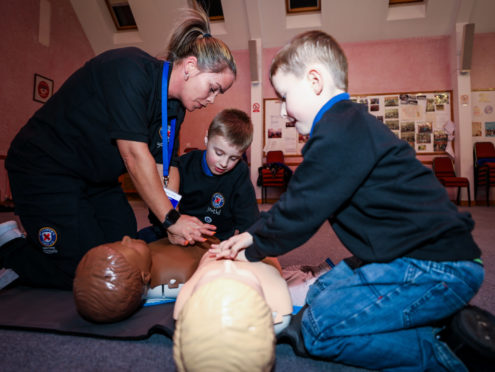 Harley and Fraser practice CPR instructed by Kelly.