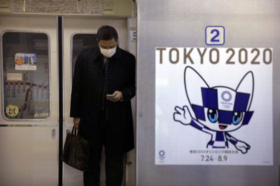 A poster promoting the Tokyo 2020 Olympics is posted next to a train door as a commuter wearing a mask looks at his phone.