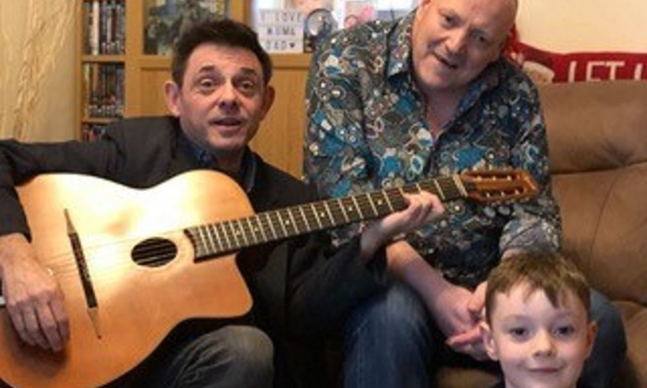Alan Reed with the guitar signed by Steve Hackett, handing it over to Kevin O' Neil and son Nathan, 6.