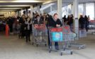 Coronavirus panic buying - hundreds of customers queue for over an hour with empty trollies zig-zaging through the car park at Costco wholesale warehouse, Sunbury-on-Thames