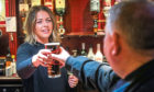 Manager Rachel Garthley serving one of the last pints to Alex Galloway in the Club Bar, Dundee, in March before lockdown.