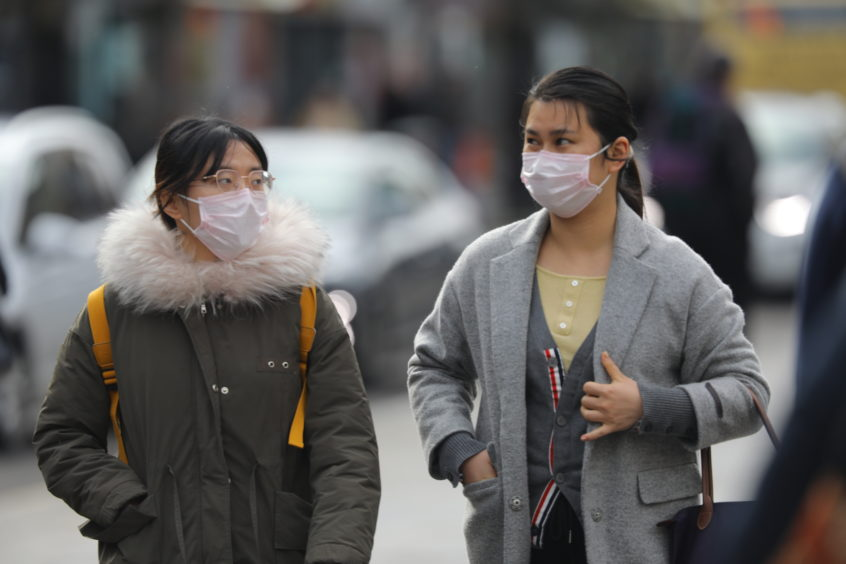 People wearing facemasks in Dundee as the country deals with the coronavirus outbreak.