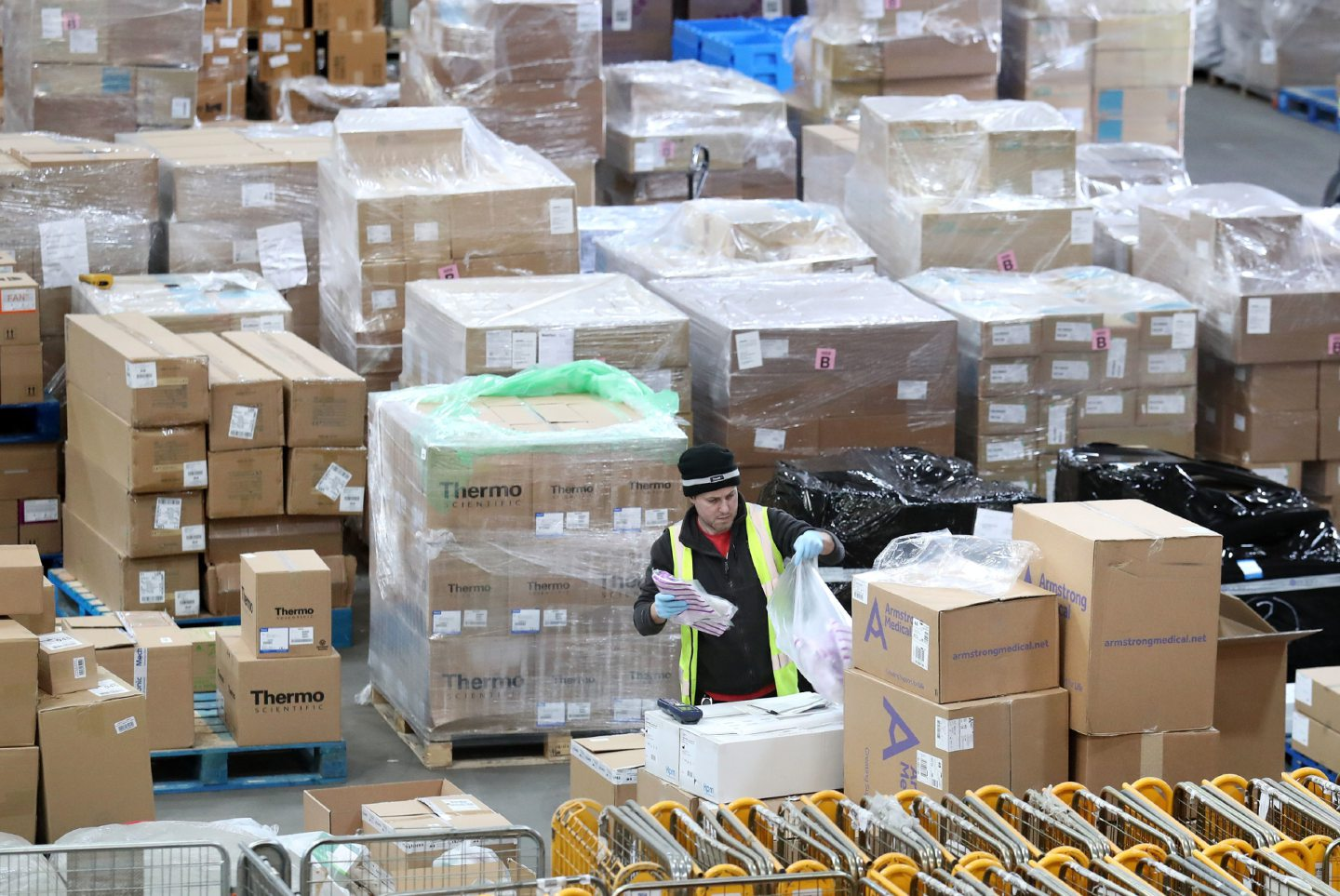 A worker gathers supplies at the NHS national procurement warehouse at Canderside, Larkhall.