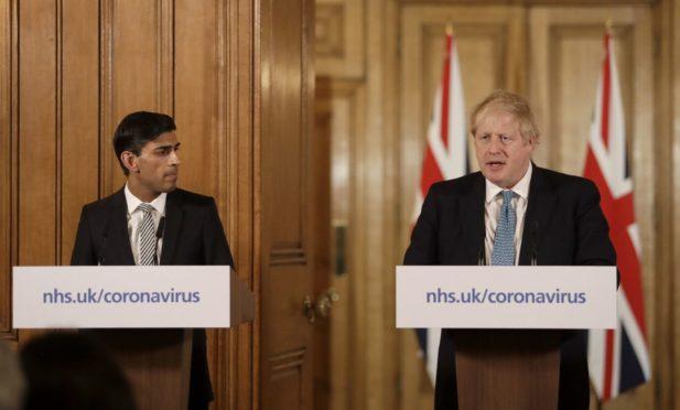 Prime Minister Boris Johnson, with Chancellor Rishi Sunak, speaking at a media briefing in Downing Street, London, on Coronavirus.