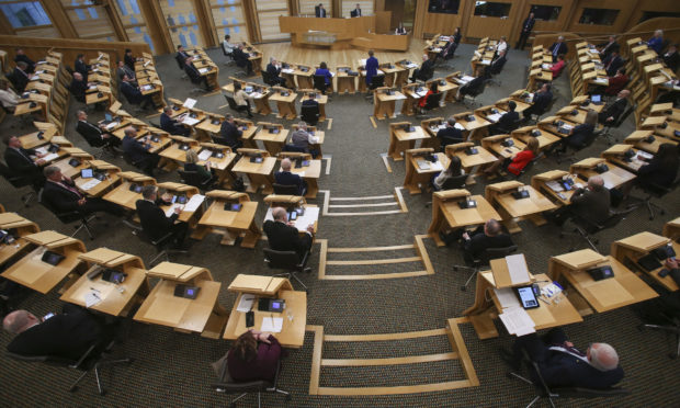 MSPs social distancing with every second seat removed at the Scottish Parliament, Holyrood.