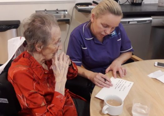 Carol Stillie, Activities Coordinator at Balhousie Rumbling Bridge helping resident Ursula Crichton write a letter.