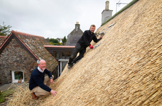 Fife Conservation Officer Matthew Price with thatcher Tomasz Obara at work on a thatched roof on Bow Road, Auchtermuchty.