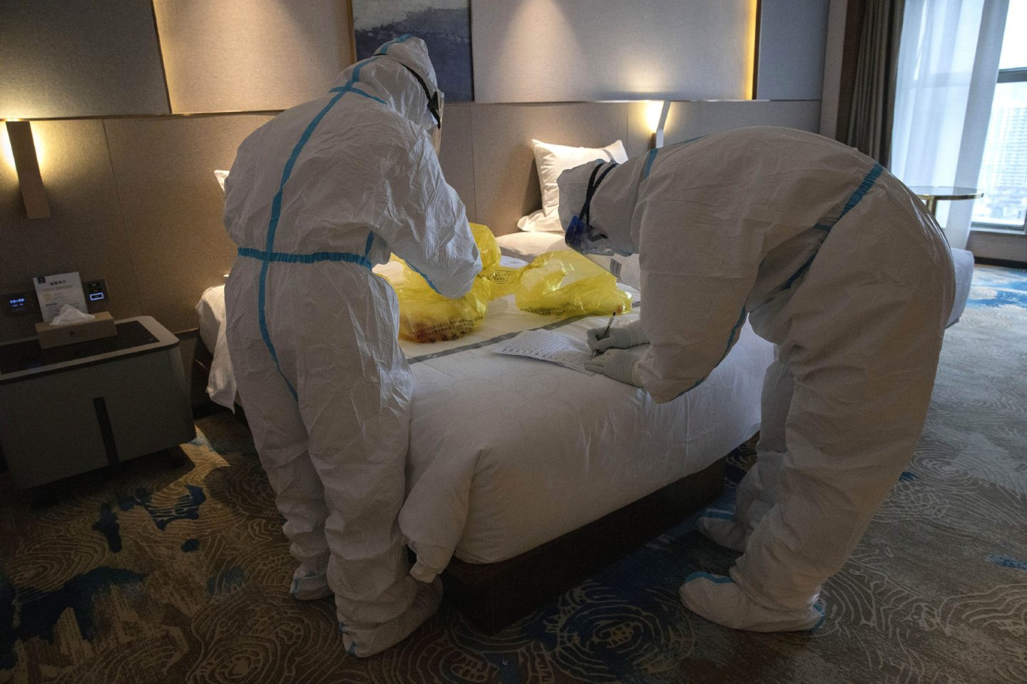 Workers in protective suits collect COVID-19 samples to test at a quarantine hotel in Wuhan in central China's Hubei province