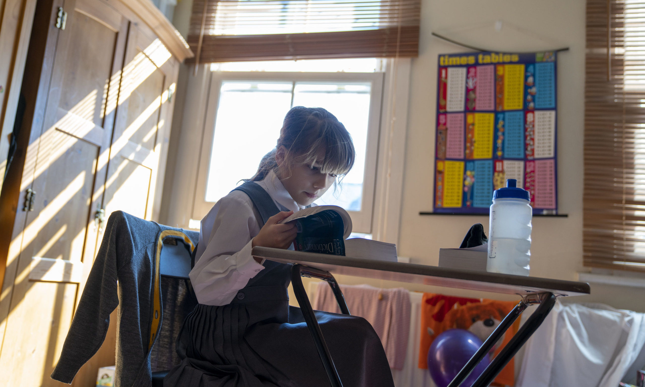 Emily, 9, sits at her desk at home on the first day of home schooling after schools shut on Friday due to the coronavirus pandemic.