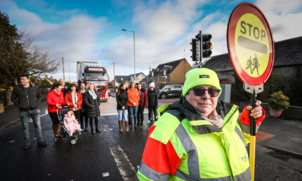 Lollipop Lady Yvonne Nicol and parents want to see the cuts reversed.