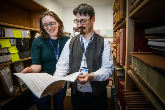 Public Engagement Officer Hope Busàk with archivist Ruaraidh Wishart in the archive room with the Ethnical Hacking workbook.