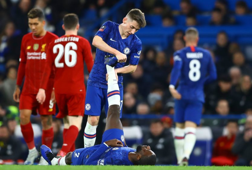 Rising star Billy Gilmour helps Chelsea team-mate Antonio Rudiger with cramp during win over Liverpool