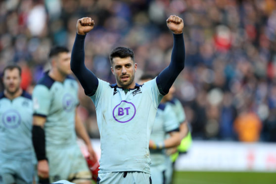 Adam Hastings celebrates at the end of Scotland's win over France.
