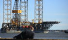 A man watches on as the rig sails down the Tay.