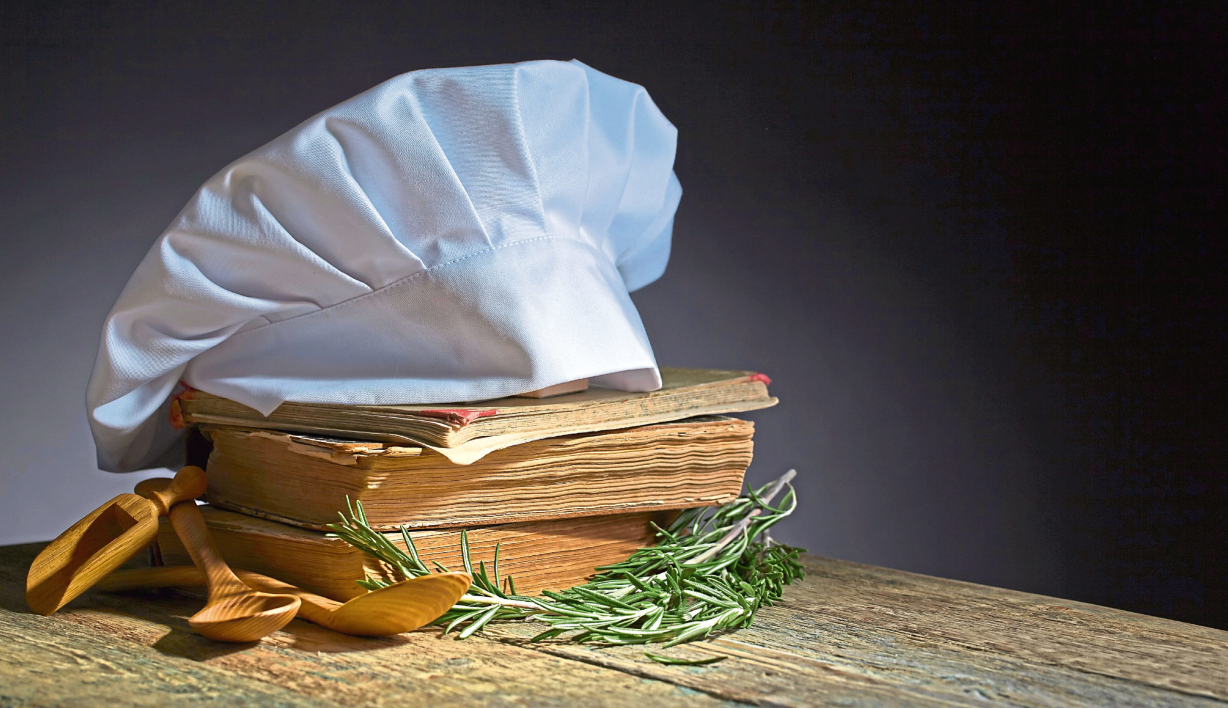 Old culinary books , chef hat and wooden spoons . Kitchen accessories on the old wooden table .; Shutterstock ID 719175079; Purchase Order: -