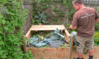 A wooden compost bin made from a kit supplied by Harrod Horticultural being filled with material suitable for home composting.