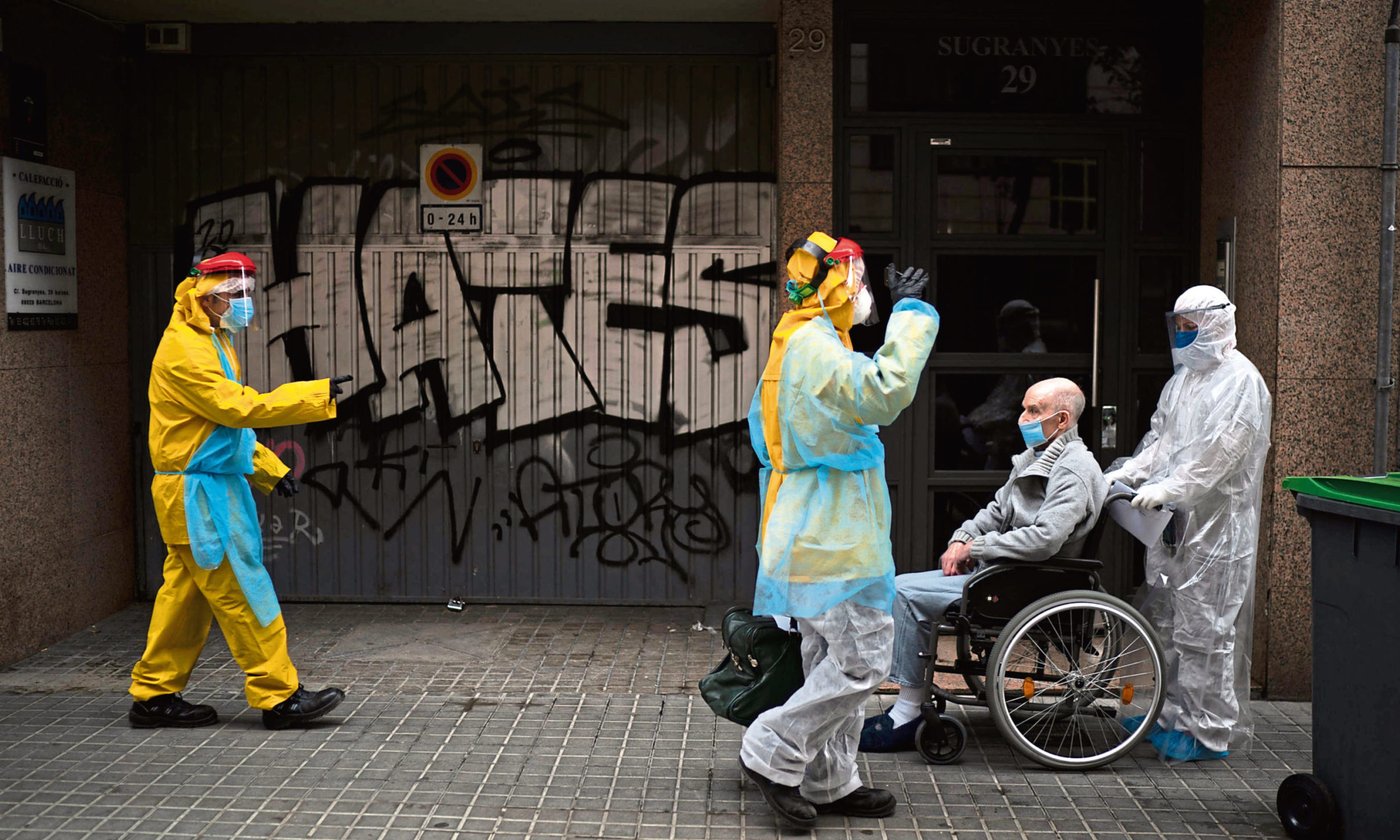 A volunteer of the Spanish NGO Open Arms pushes in a wheelchair an elderly resident of a nursing home with coronavirus symptoms to an ambulance in Barcelona, Spain.