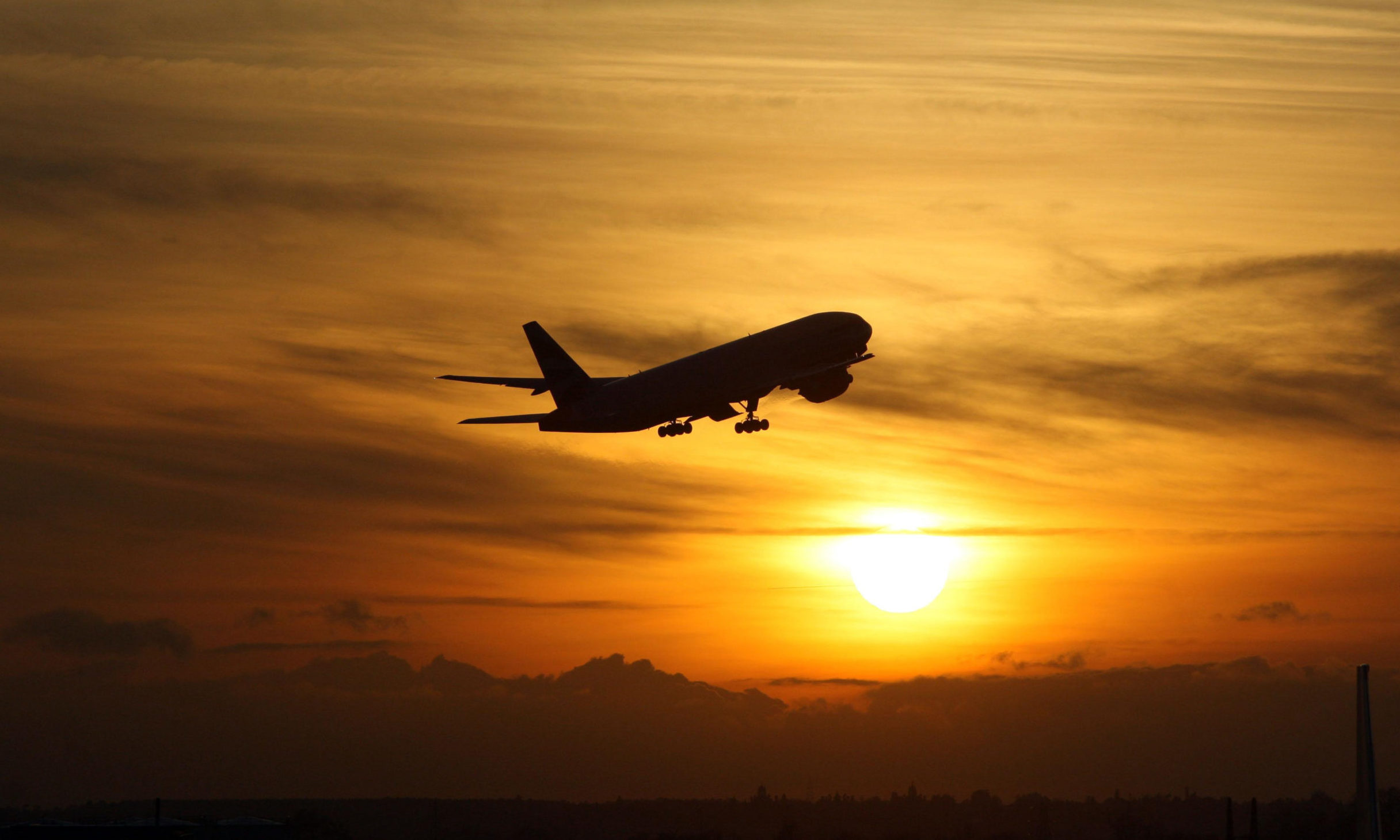A plane taking off from Heathrow Airport at sunse.